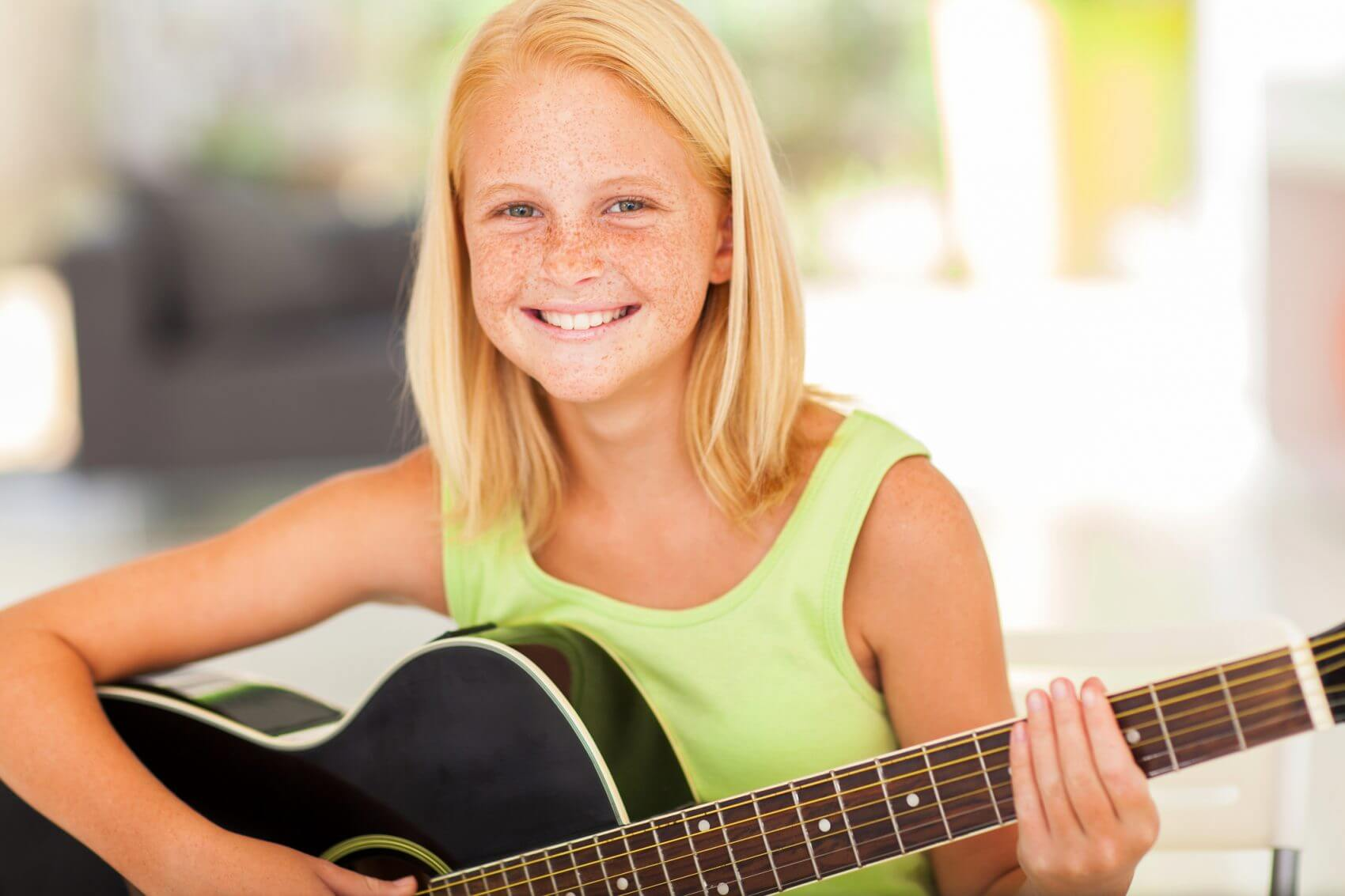 Happy girl playing guitar at The Conservatory of Music in Katy TX